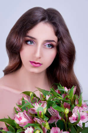 gray eyes: Young woman with gray eyes, long brown hair and bare shoulders holding pink flowers