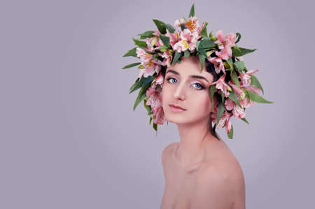 Young woman wearing pink flowers on her head on lavender background photo