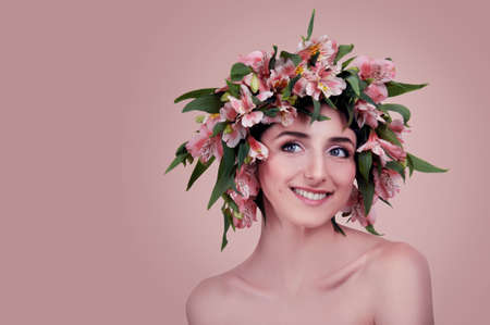Young woman wearing pink flowers on her head isolated on white photo
