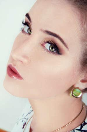 ojos verdes: Hermosa mujer sexy con el maquillaje del día natural y brillantes ojos verdes que llevan pendientes verdes Foto de archivo