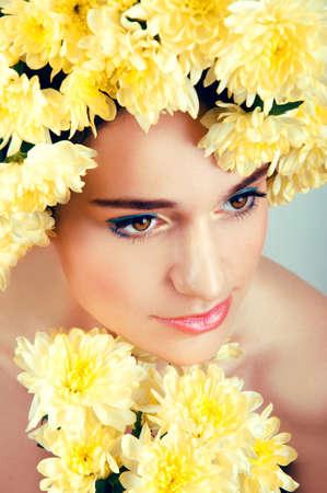 ojos marrones: Mujer de raza blanca con los ojos de color marr�n con flores de color amarillo guirnalda alrededor de su cabeza