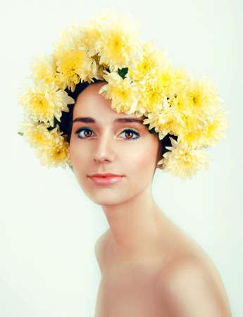 ojos marrones: Muchacha con la guirnalda de flores. Mujer de raza blanca con ojos marrones y cabello casta�o de cerca sobre fondo blanco Foto de archivo