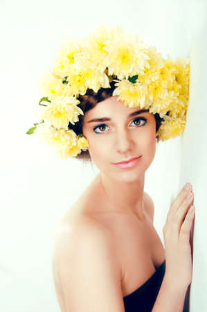 Girl with flower wreath. Caucasian woman with suntanned glowing skin and  brown hair close up