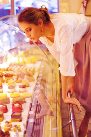 shop display: Woman choosing cakes and desserts in a cafe, sitting near the shop display