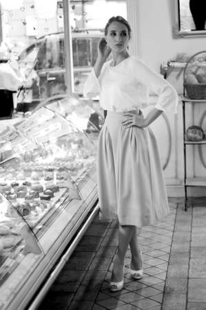 shop display: Woman choosing cakes and desserts in a cafe, standing  near the shop display
