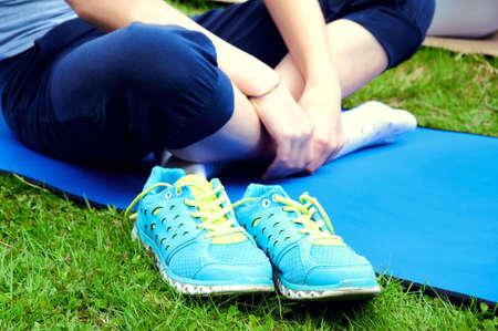 crosslegged: Girl sitthing on a yoga mat crosslegged with ker blue sneakers on the grass