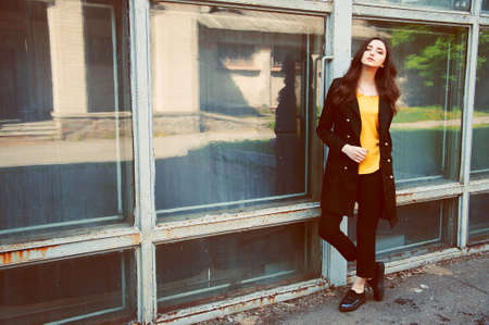 Young woman portrait with long brown hair dressed in black trenchcoat and yellow blouse Stock Photo