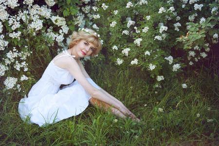 sundress: Beautiful blonde woman in white sundress sitting on the grass near white flowers
