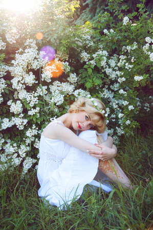 beautiful blonde girl with green eyes: Beautiful blonde woman in white sundress sitting on the grass near white flowers