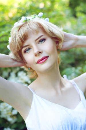 sundress: Beautiful blonde woman in white sundress posing in garden wearing circlet of flowers