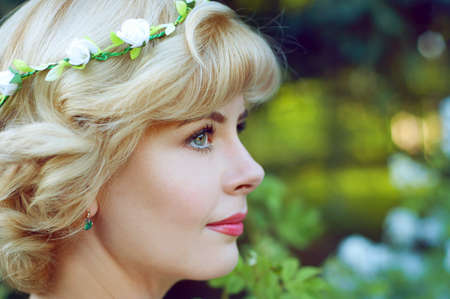 Beautiful blonde woman in white sundress posing in garden wearing circlet of flowers