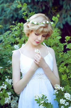circlet: Beautiful blonde woman in white sundress posing in garden wearing circlet of flowers