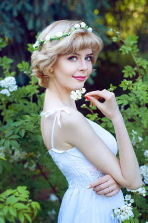 circlet: Bella donna bionda in posa prendisole bianco in giardino indossando circlet dei fiori Archivio Fotografico