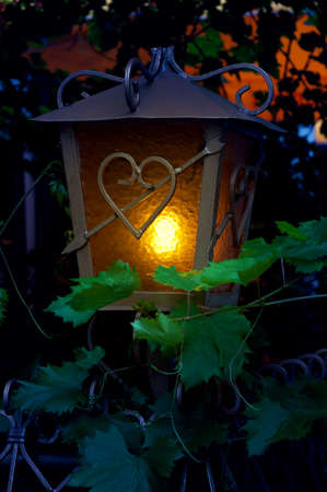 glass heart: Street lantern in twilight hour with a heart shape symbol. Summer nights.