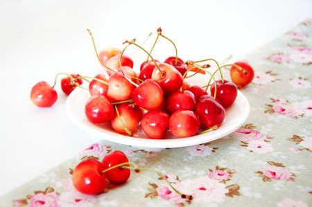 sweet treats: Summer rainier cherries on a plate on a tablecloth. Sweet treats.