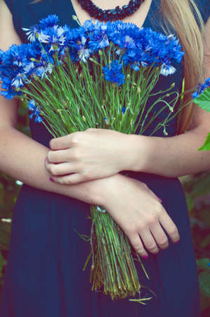 blue dress: Woman in blue dress holding a bouquet of cornflowers. Outdoor portrait.