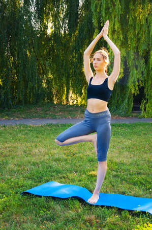 Sportswoman doing yoga exercises, standing in a tree pose