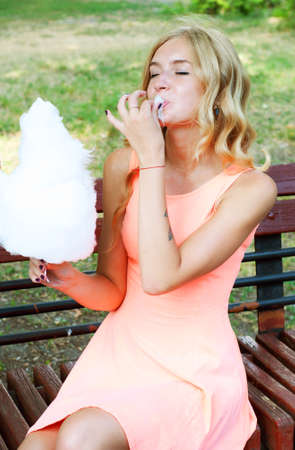algodon de azucar: Beautiful blonde woman enjoying cotton candy. Summer treats.