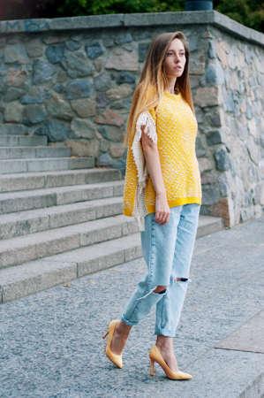 de vaqueros: Calle chica pelirroja de moda de la ciudad con el pelo largo que llevaba amarillo poncho y pantalones vaqueros boyfriend Foto de archivo
