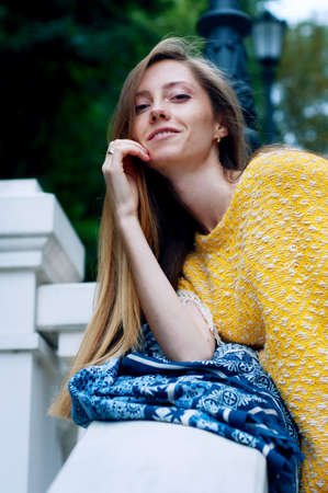 redheaded: Street city fashion redheaded girl with long hair wearing yellow poncho and boyfriend jeans