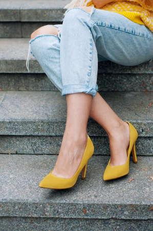 Stadsstraat fashion outfit met gele poncho, hoge hakken en boyfriend jeans Stockfoto
