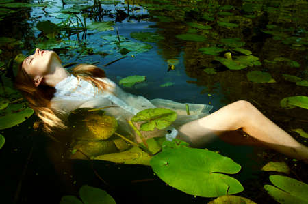 nenuphar: Tender young woman swinning in the pond amon water lilies basking in the sun in shallow waters