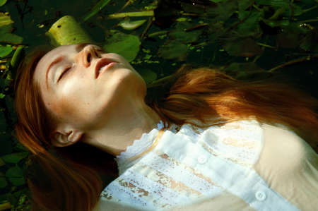 Tender young woman swinning in the pond among water lilies basking in the sun in shallow waters