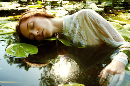 sexy female body: Tender young woman swimming in the pond among water lilies basking in the sun in shallow waters
