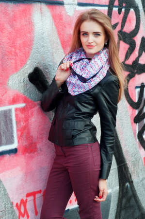 light complexion: Young fashionable woman in black leather jacket and sunglasses wearing pink scarf and smiling Stock Photo