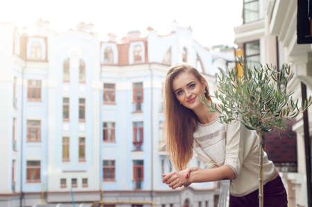 light complexion: Young blonde woman on her balcony smiling. Urban cityscape and modern buildings.
