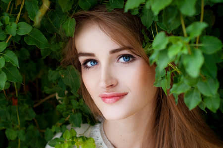 light complexion: Happy smiling beautiful young woman surrounded by green leaves with blue eyes