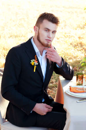 engagement party: Handsome groom sitting at the wedding table. Engagement party. Outdoor portrait. Stock Photo