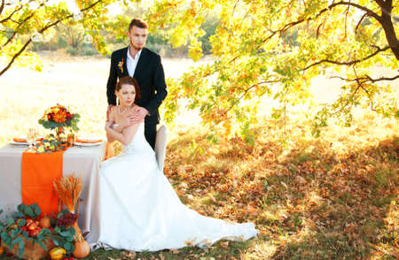 Bride and groom at the wedding table. Autumn outdoor setting. Romantic scenery.
