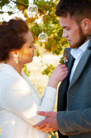 pinning: Young wife pinning buttonhole flowers to grooms coat at the wedding reception Stock Photo