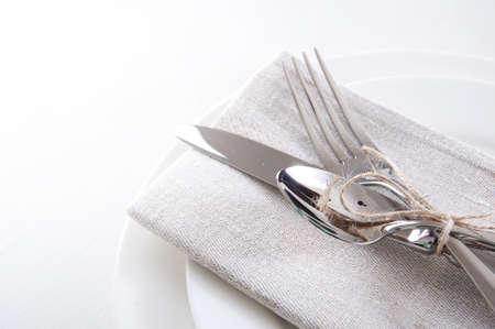 Tabella impostazione nei colori bianco e grigio con tovaglioli di lino e posate