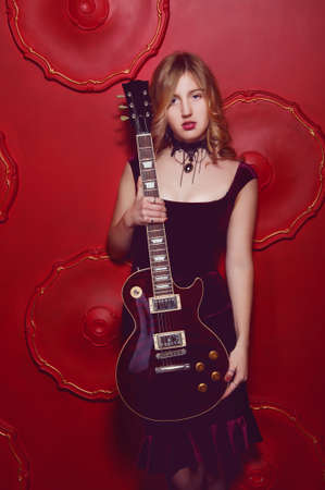 velvet dress: Sensual blonde woman in purple velvet dress holding electric guitar Stock Photo