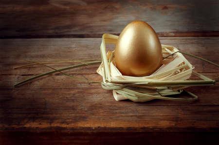 golden egg: Golden egg on wooden table in  straw nest closeup