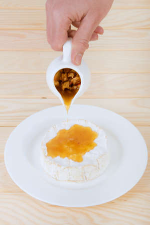 adding: Camembert cheese with honey sauce with nuts and butter. Waiter adding sauce to the dish.