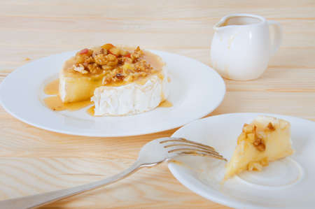 man nuts: Camembert cheese with honey sauce with nuts and butter. Waiter slicing the cheese.