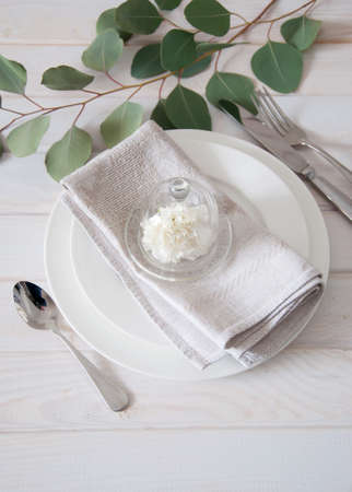 elegantly: Elegantly served table with gray linen napkins and silverware decorated with white carnation flower and eucalyptus leaves