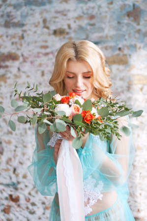 boudoir: Charming young blond woman with curly hair holding fresh flowers bouquet with roses, carnations and eucalyptus leaves. Bridal boudoir.
