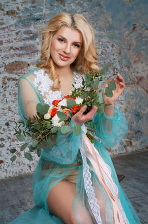 Charming young blond woman with curly hair holding fresh flowers bouquet with roses, carnations and eucalyptus leaves. Bridal boudoir.
