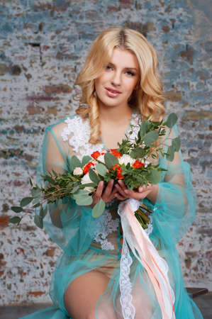 bridal hair: Charming young blond woman with curly hair holding fresh flowers bouquet with roses, carnations and eucalyptus leaves. Bridal boudoir.