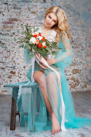 boudoir: Charming young blond woman pregnant with curly hair holding fresh flowers bouquet with roses, carnations and eucalyptus leaves. Bridal boudoir.