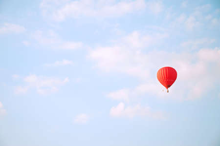 air baloon: Red hot air baloon flying in blue sky with white clouds