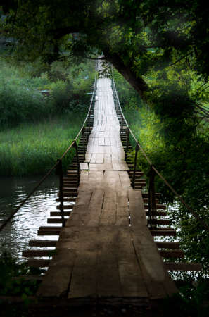 bridge in nature: Old suspension bridge in an old maountain village in sunset light in summer