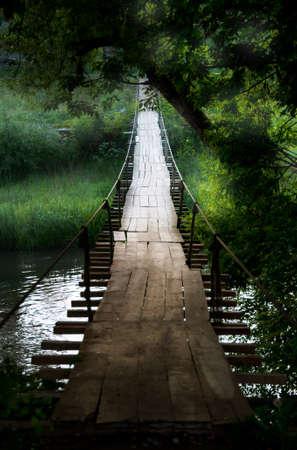suspenso: Puente de suspensión viejo en un antiguo pueblo maountain a la luz del sol en verano