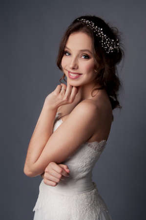 brown hair blue eyes: Adorable young bride with brown curly hair, blue eyes and white dress and pearl headpiece with bare shoulders