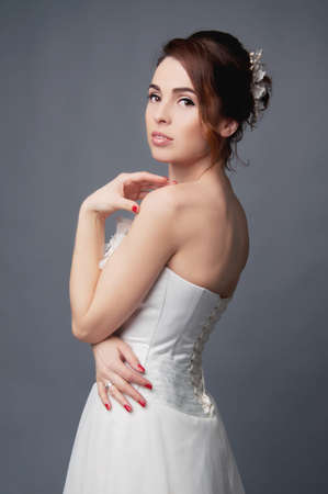 hair studio: Elegant bride with brown short hair updo and bare shoulders white wedding dress