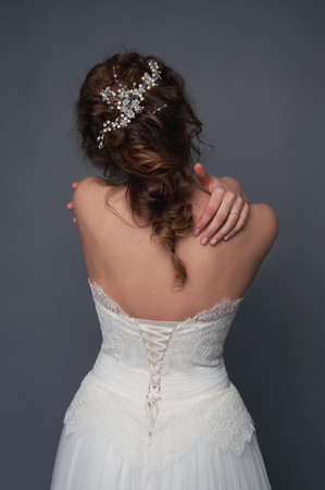 headpiece: Bridal fashion. Brunette bride with pearl headpiece and white wedding gown view from the back. Stock Photo